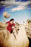 The Concubine. Woman alone in a desert wearing a red dress Royalty Free Stock Image