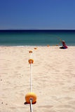 Woman on deserted white beach with calm blue sea. royalty free stock image