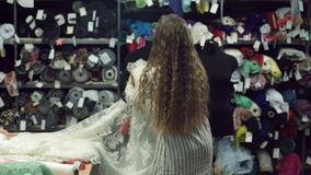 Woman design wedding dress based on lace on mannequin in salon. Lady with long curly blond hair in white blouse with black stripes, pincushion on left hand stock video footage