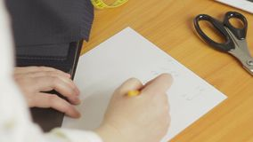A woman, a designer of clothes, draws a sketch with a pencil and writes the calculations of a new product. Close-up