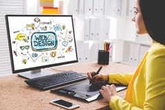Woman designer drawing a web design sketch. Side view of a young woman in a yellow shirt drawing a stylish colorful web design sketch on her desktop computer royalty free stock photography