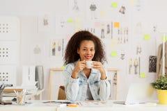 Woman designer drinking coffee Stock Image