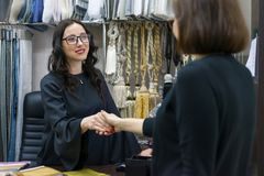 Woman designer, interior decorator smiles and greets with the client. Small business textile store. Woman designer, interior decorator smiles and greets with royalty free stock image
