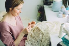 Woman designer knitting tender dress with crochet. Close up. Female freelancer creative working at cozy home workplace. royalty free stock image