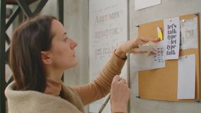 A woman designer standing at the wall attaches her ideas to the wall, color selection and coloristics. Choosing a color