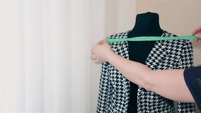 Woman designer women`s clothing makes a measurement on a black and white jacket 1080. Woman designer women`s clothing makes a measurement on a black and white stock video footage