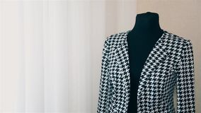 Woman designer women`s clothing makes a measurement on a black and white jacket HD. Girl designer women`s clothing makes a measurement on a black and white stock video