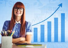 Woman at desk with arms folded against blue graph. Digital composite of Woman at desk with arms folded against blue graph Stock Image