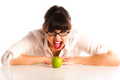 Woman at desk with a green apple wearing glasses Stock Images