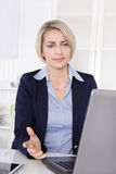 Woman at desk has problems with computer. Stock Photography