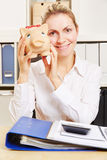 Woman at desk holding piggy bank Royalty Free Stock Photo