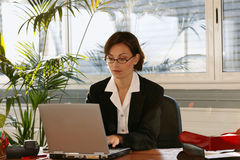 Woman at desk with laptop computer Stock Photography