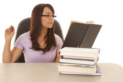 Woman at desk with a stack of books hand up Royalty Free Stock Photography