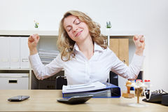 Woman at desk stretching Stock Photography