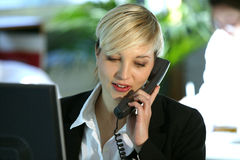 Woman at desk with telephone. Young blond business woman sitting at her desk and chatting on the phone Stock Photo
