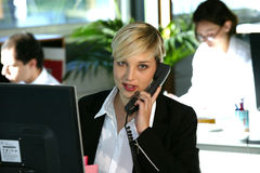 Woman at desk with telephone. Young blond business woman sitting at her desk and chatting on the phone Stock Photos