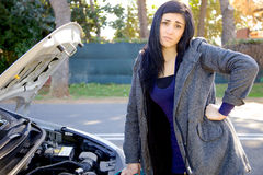 Woman desperate about broken car looking camera Stock Photos