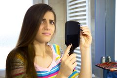 Woman desperate about hair loss in front of mirror in bathroom looking camera sad. Unhappy woman finding hair in brush royalty free stock images