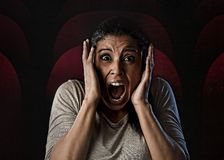 Woman desperate and scared terrorized at cinema hall watching horror movie Stock Images