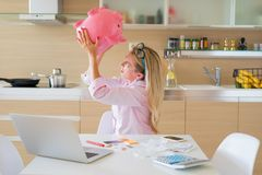 Woman desperately searhing for some money in piggy bank Stock Images