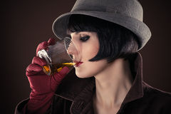 Woman detective drinking whiskey. Attractive woman detective drinking whiskey from a glass stock photos
