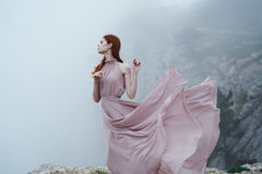 Woman with a developing dress on a cliff face, foggy weather.  Stock Photography