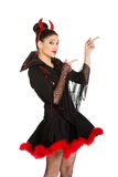 Woman in devil carnival costume pointing aside. Stock Images