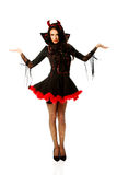 Woman in devil clothes with open hands gesture Royalty Free Stock Photo