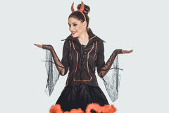 Woman in devil costume with empty hands. Stock Image