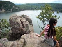 Young Asian Woman Atop Boulders at Devil`s Lake, Wisconsin. A young Asian woman wearing sunglasses sits atop a boulder at Devil`s Lake, Wisconsin Stock Photo