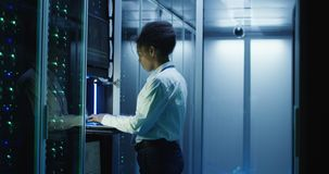 Woman diagnosing server hardware in center. African American female IT worker diagnosing server hardware in modern data server with rows of server racks stock image