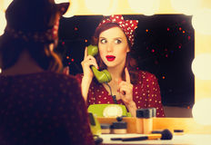 Woman with dial phone applying cosmetics Royalty Free Stock Photo