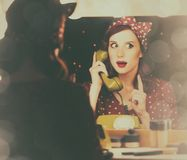 Woman with dial phone applying cosmetics. Portrait of a beautiful surprised woman with a dial phone and applying cosmetics near a mirror. Photo in retro color Stock Images