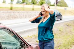 Woman dialing her phone after car crash. Woman dialing her phone after car accident royalty free stock images