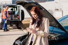 Woman dialing her phone after car breakdown. Problem mechanic crash Stock Image