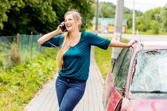 Woman dialing her phone after car crash Stock Photography