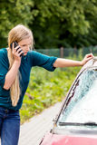 Woman dialing her phone after car crash Royalty Free Stock Photography