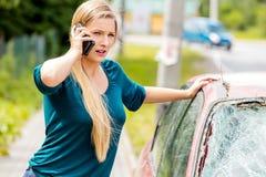 Woman dialing her phone after car crash Stock Image
