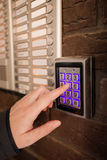 Woman dialing passcode on security keypad intercom. To open entrance door of the apartment building Stock Photos
