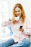 Woman dialing phone and drinking coffee Stock Photo