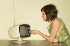 Woman dialing television. Stock Photo