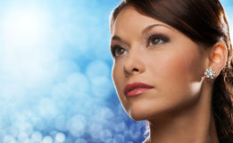 Woman with diamond earring over blue lights Royalty Free Stock Photos