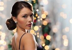 Woman with diamond earring over christmas lights Royalty Free Stock Photo