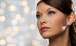 Woman with diamond earring over holidays lights Stock Photography