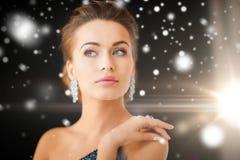 Woman with diamond earrings. Jewelry, luxury, vip, nightlife, party concept - beautiful woman in evening dress wearing diamond earrings Stock Photo