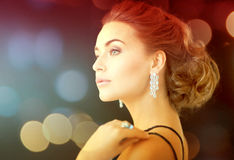 Woman with diamond earrings. Jewelry, luxury, vip, nightlife, party concept - beautiful woman in evening dress wearing diamond earrings Royalty Free Stock Photos