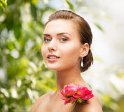 Woman with diamond earrings, ring and flower Stock Image