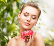 Woman with diamond earrings, ring and flower Royalty Free Stock Images