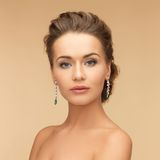 Woman with diamond and emerald earrings Stock Images