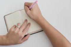 Woman with diamond ring writing in a diary Stock Photography